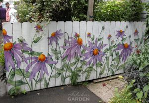 Purple echinacea painted on this white fence allude to the amazing garden within