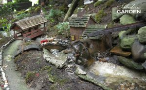 This miniature village features a running water wheel